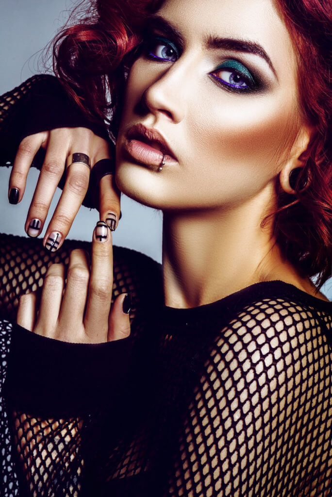 Beautiful gothic girl hipster model with piercings, with red hair, make-up art in black svitshote in the studio
